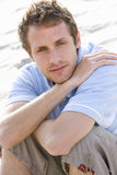 Portrait of young man sitting at beach Stock Image