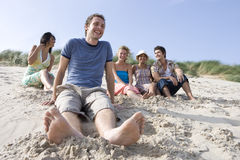 Portrait of young man sitting at beach, friends in background stock images