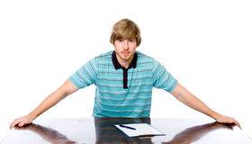 Portrait of a young man sitting behind a desk. Royalty Free Stock Photos