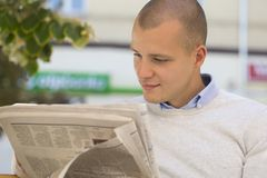 Portrait of young man while sitting on the bench and read newspa Stock Photo
