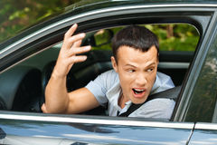 Portrait young man sitting car. Looking out window looks back indignantly background summer green park Royalty Free Stock Photos