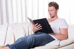 Portrait young man sitting on couch and reading in a book Stock Photos