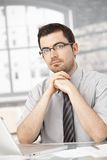 Portrait of young man sitting at desk using laptop Royalty Free Stock Photos