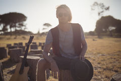 Portrait of young man sitting by guitar on tree stump Royalty Free Stock Image
