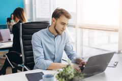Portrait of young man sitting at his desk in the office royalty free stock images