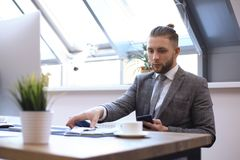 Portrait of young man sitting at his desk in the office royalty free stock image