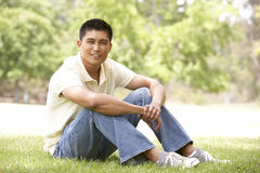 Portrait Of Young Man Sitting In Park Royalty Free Stock Photography