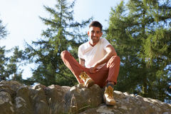 Portrait Of Young Man Sitting On Rock Stock Photography