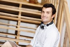 Portrait of young man sitting at the stairs in office Stock Photo