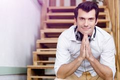 Portrait of young man sitting at the stairs in office Stock Images