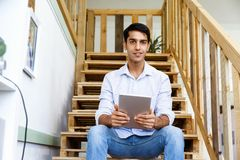 Portrait of young man sitting at the stairs in office Royalty Free Stock Photo