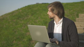Portrait of Young Man Sitting On The Stairs In Park Using Laptop. Outdoors, 4K stock video footage