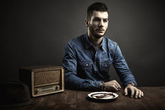 Portrait of young man sitting at a table, vintage style Royalty Free Stock Images