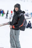 Portrait of  a Young man skier on the ski slope. Portrait of  a Young man skier on the slope ,bringing  the  skis in a hand Royalty Free Stock Image