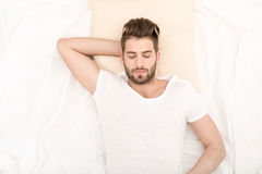 Portrait of young man sleeping. Portrait of a young man from above sleeping in a white bed Stock Image