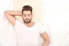 Portrait of young man sleeping. Portrait of a young man from above sleeping in a white bed Royalty Free Stock Photos