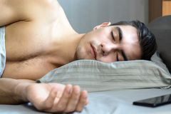 Portrait of a young man sleeping in bed on an orthopedic pillow is a special shape for a healthy spine royalty free stock photos