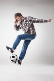 Portrait of young man with smart phone and football ball. On gray background. concept of continuous soccer practice royalty free stock photo
