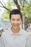 Portrait of young man smiling on city street, looking at camera Royalty Free Stock Photos