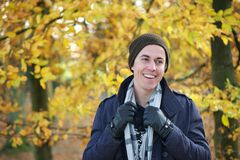 Portrait of a young man smiling outdoors in jacket gloves hat scarf Stock Image