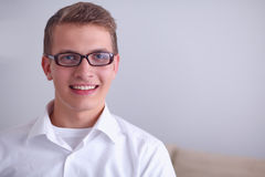 Portrait of young man smiling sitting on gray Stock Photos