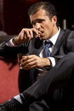 Portrait of young man smoking cigar and holding wineglass Royalty Free Stock Photos