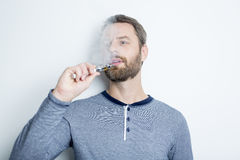 Portrait of a young man smoking electric cigarette Stock Images