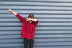 Portrait of a young man standing on the background of a gray wall and throwing dab royalty free stock images