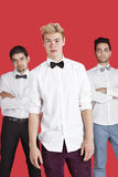 Portrait of a young man standing in front of male friends over red background Royalty Free Stock Image