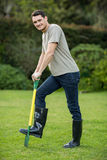 Portrait of young man standing with a gardening rake Royalty Free Stock Images