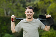 Portrait of young man standing with a gardening shovel Stock Image