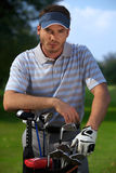 Portrait of young man standing by golf bag full of sticks Stock Photography