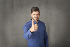 Thumbs up. Portrait of a young man standing at grey wall and giving thumbs up royalty free stock photography