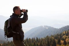 A traveler in the mountains looks in the binoculars. Portrait of a young man standing on a mountain hill and looking into the binoculars in the distance stock images