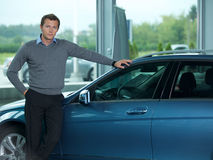 Portrait of young man standing by new car Royalty Free Stock Photography