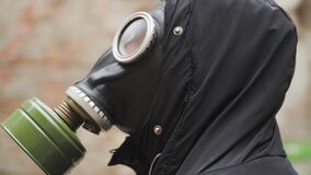 Portrait young man stands in a gas mask and looks around. Doomsday concept. Shooting on Steadicam