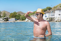 Portrait of young man with straw hat   in the sea Royalty Free Stock Photo