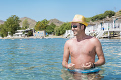 Portrait of young man with straw hat   in the sea Stock Photography