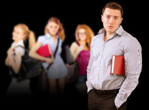 Portrait of young man-student against three girls Stock Photo