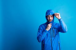 Portrait of a young man in a studio with anorak on a blue background. Portrait of a young man in a studio with blue anorak on a blue background, hood on his royalty free stock photo