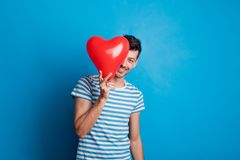 Portrait of a young man in a studio on a blue background, hiding behind red heart. Portrait of a young man in a studio on a blue background, hiding behind a red Stock Photo