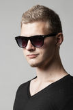 Portrait of young man in sunglasses  on gray Royalty Free Stock Photography