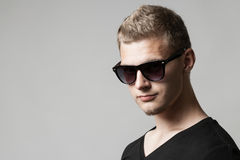 Portrait of young man in sunglasses  on gray Royalty Free Stock Photo