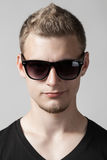 Portrait of young man in sunglasses isolated on gray Royalty Free Stock Photo