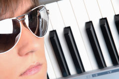 Portrait of young man in sunglasses with piano Royalty Free Stock Photos