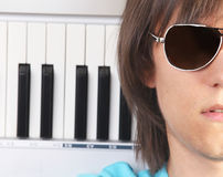 Portrait of young man in sunglasses with piano Stock Images