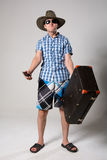 Portrait of young man in sunglasses with a suitcase in hand. Royalty Free Stock Photo