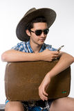 Portrait of young man in sunglasses with a suitcase. Royalty Free Stock Photography