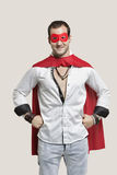 Portrait of young man in superhero costume with hands on hip standing against gray background Stock Images