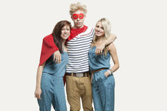 Portrait of young man in superhero costume and women wearing jumpsuits standing together against gray background Royalty Free Stock Image